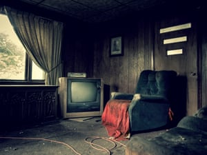 A bleak living room complete with an old television set and armchair