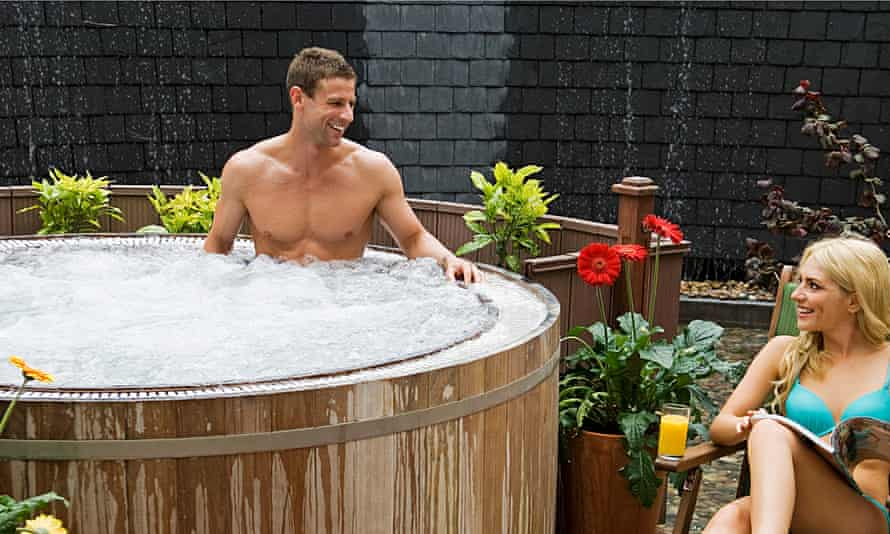 man in a bubbling hot tub smiling at a woman in a bikini on a lounge chair