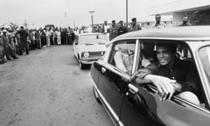 Muhammad Ali passes by a cheering crowd in Kinshasa, Zaire, on September 28, 1974 before his world heavyweight championship fight against champion George Foreman.