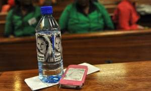 Bottled water and a mobile phone bearing the face of Reeva Steenkamp is seen in the Pretoria high court.