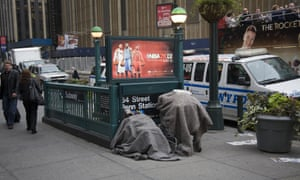 A homeless man huddles with his possessions by a subway entrance on 8th Avenue in New York City.