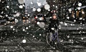 A woman rides her bike in heavy snow in Copenhagen.