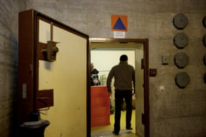 A guard from the private security firm stands at the entrance door of the shelter
