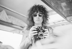 Singer Marc Bolan of T-Rex holding a Nikon camera on a tour bus during a four-date British tour, June 1972