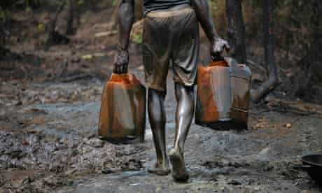 A man carries oil at a refinery in Bayelsa, Nigeria