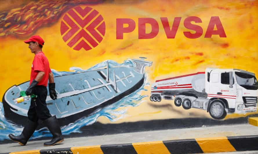 A worker walks past a mural with a PDVSA logo at a petrol station in Caracas