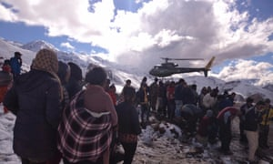 People gather near a Nepal army helicopter being used to rescue avalanche victims in the Annapurna region.