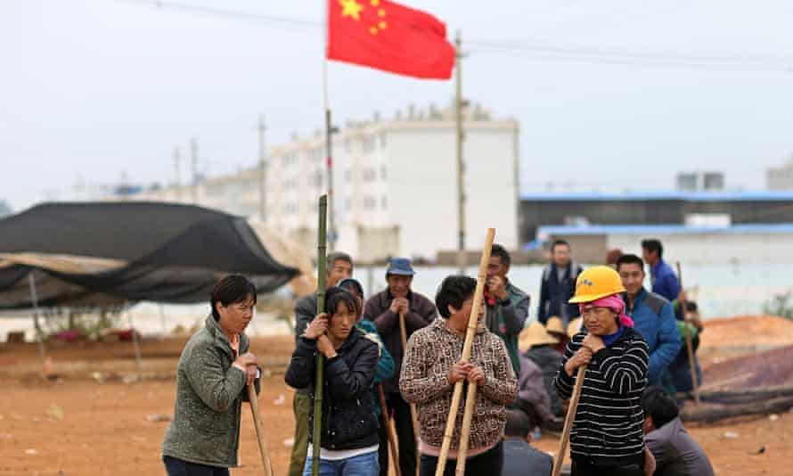 Villagers guard the entrance to Fuyou village in Yunnan province where the violence took place
