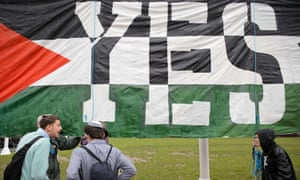 Young pro-Israel men argue with pro-Palestine supporters beside a giant banner calling for a recognised Palestinian state.