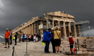 Tourists walk by the Parthenon atop the ancient hill of the Acropolis during a rainy day
