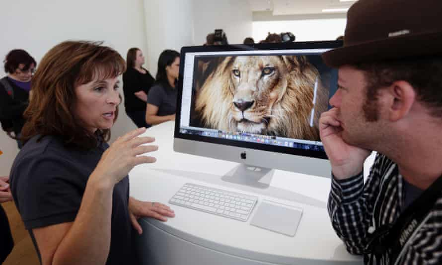 An apple employee, at left, explains the features of the new iMac at Apple headquarters on Thursday, Oct. 16, 2014 in Cupertino, California.