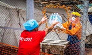 A healthcare worker wearing protective gear hands out water bottles at a treatment centre in the west of Freetown, Sierra Leone.