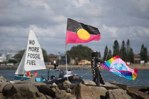 A protester erects a flag at Horseshoe beach, Newcastle, for the protest against Australia's fossil fuel industry.