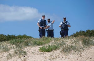 Police watch the protest from Horseshoe beach.