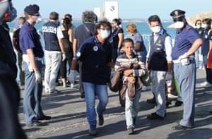 A rescuer helps a child immigrant disembark an Italian military ship in Pozzallo, Sicily