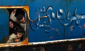 Would-be immigrants look out of a window from a fishing ship as they arrive at Catania harbour