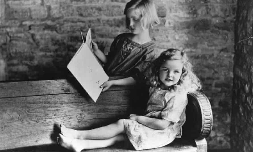 Unity Mitford, nine, reading with sister Jessica, six, in the garden of their house in Asthall.