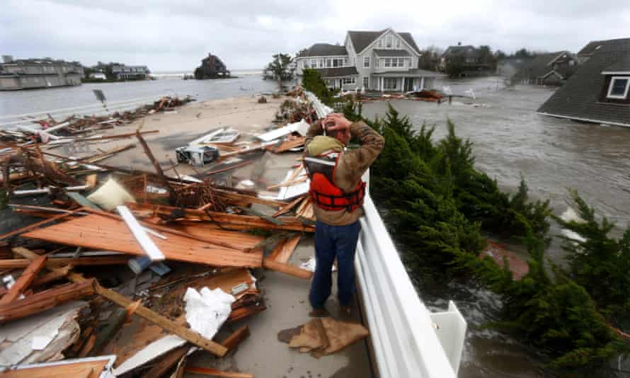 In this Oct. 30, 2012 file photo, Brian Hajeski, 41, of Brick, N.J., reacts as he looks at debris of a home that washed up on to the Mantoloking Bridge the morning after superstorm Sandy rolled through in Mantoloking, N.J. S