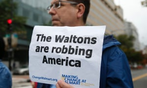 Holding a sign, a man joins Walmart employees and supporters as they block off a major intersection near the Walton Family Foundation in downtown Washington October 16, 2014.