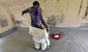 A health worker removes her protective gear inside a tent in an Ebola unit in the Ivory Coast