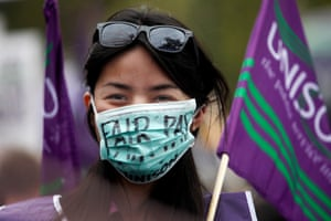 A woman wears a medical mask with the words 'Fair Pay' written on it.