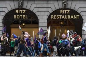 Protestors walk past the Ritz Hotel.
