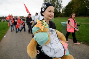 A woman carries a protest bear against falling real wages.