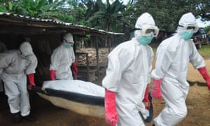 A burial team in protective gear carry the body of woman suspected to have died from Ebola in Monrovia, Liberia.