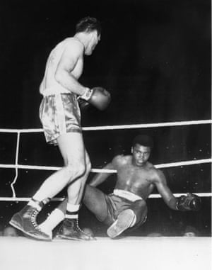Clay is floored by British boxer Henry Cooper during their fight at Wembley Stadium in 1963. Only a delay caused by a torn glove would allow Clay to regain his composure and eventually win the fight with a fifth round stoppage.