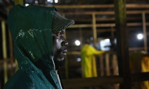 A security guard watches as construction workers build a new Ebola isolation and treatment centre in Monrovia, Liberia.
