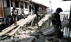Colombian navy special forces on patrol among stilted waterfront shacks in Buenaventura