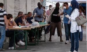 Italian authorities prepare to register rescued African migrants as they arrive in Palermo after a rescue mission.