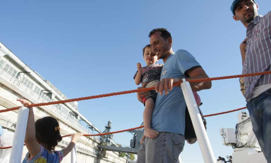Two men and children disembark from a boat at the Brindisi harbor, southern Italy.