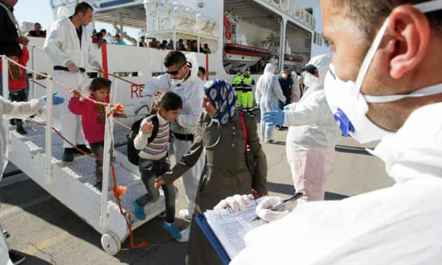 Women and children are being helped off a boat following a rescue mission in Italy.