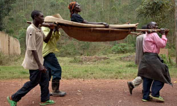 An HIV-positive Congolese woman is carried to hospital on a stretcher