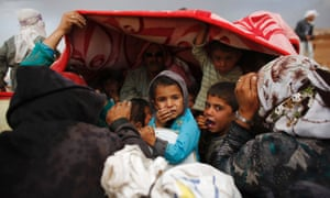 Syrian Kurdish refugees shield themselves from rain after crossing into Turkey from the Syrian border town Kobani. Ankara has been under pressure to take a tougher stance against Isis.