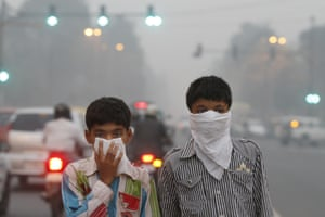 Children cover their faces as a precaution from the air pollution, New Delhi, India.