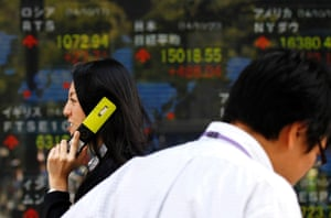 A pedestrian holding her mobile phone walks past an electronic board showing the stock market indices of various countries outside a brokerage in Tokyo October 20, 2014.
