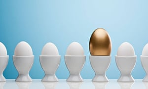 Golden egg in an egg cup with others around