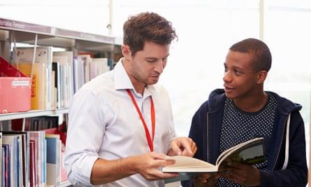 Male teacher helping student
