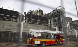 A fire engine is parked in front of a fire damaged part of the Didcot B power station