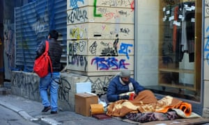 A homeless man sits on the pavement near Syntagma Square in Athens.