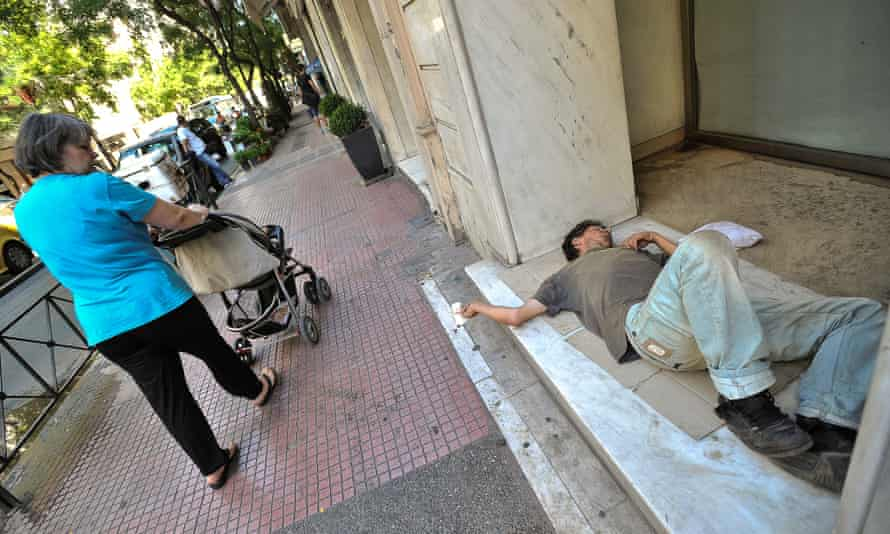 A homeless man sleeps in front of a shop in Athens.