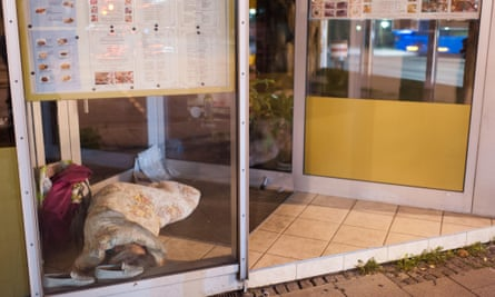 A homeless person sleeps in the entrance to a restaurant in Munich.