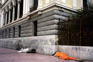 Homeless people sleep on Panapestimiou Street in Athens.