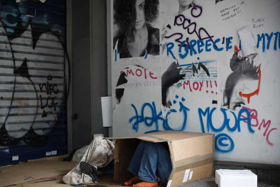 A homeless man uses a cardboard box for shelter in an alleyway in Athens.