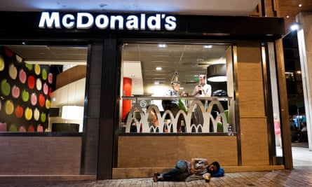 A man sleeps in front of a McDonald's restaurant in central Athens.