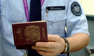 An immigration officer checking a passport from a passenger arriving at Heathrow airport.