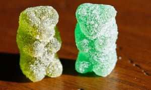 A marijuana-infused sour gummy bear candy is shown next to a regular one in Golden, Colorado.