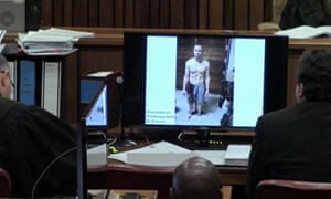 An image from the court showing on screen a police photograph of Oscar Pistorius standing on his blood-stained prosthetic legs.